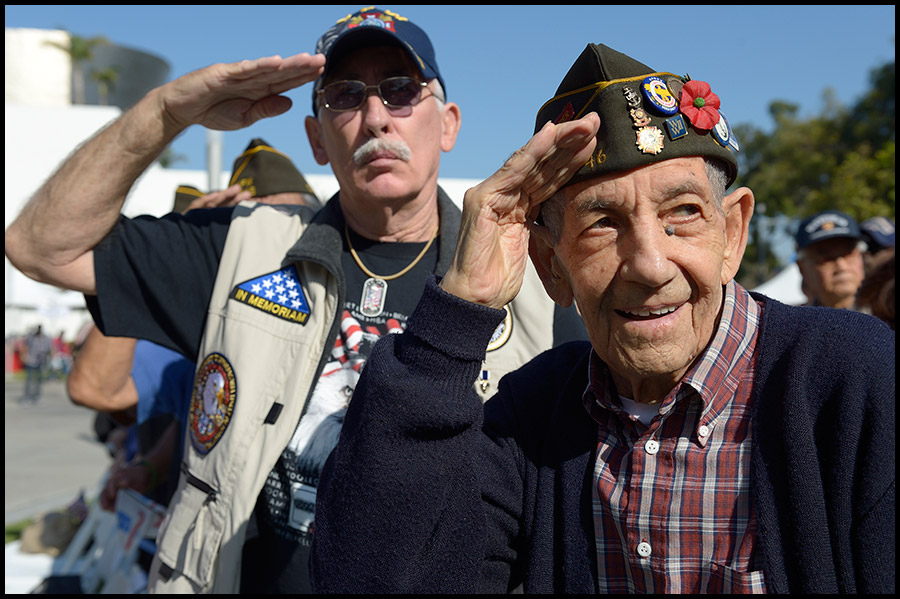 World War II Navy veteran Ralph Barbero, right, and Korean war vet Tom Tislow salute during a Veteran's Day ceremony at the Cerritos Civic Center on Monday.